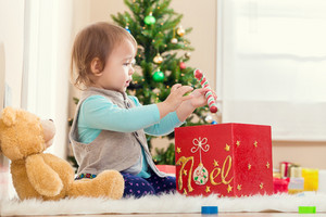 Little toddler girl playing with her presents under the Christmas tree