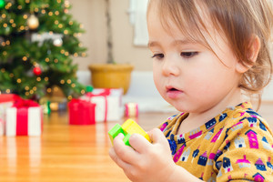Little toddler girl playing with her toys in front of the Christmas tree and present boxes