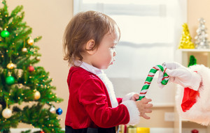 Little toddler girl receiving a candy cane from Santa Claus by the Christmas tree
