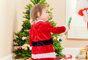 Little toddler girl receiving a gift from Santa Claus by the Christmas tree