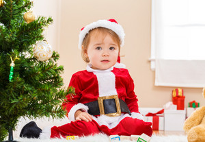 Little toddler girl sitting by the Christmas tree with a santa costume