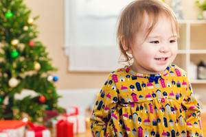 Little toddler girl smiling in front of a Christmas tree