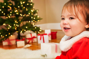 Little toddler girl smiling in front of the Christmas tree
