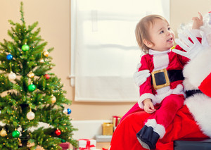 Little toddler girl talking to Santa Claus by the Christmas tree