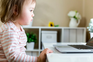 Little toddler girl using her laptop computer