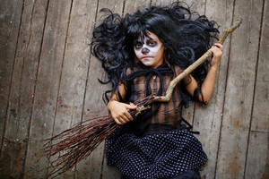 Little witch in wig and Halloween attire lying on wooden floor with broom