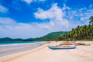 Local boats on wide Nacpan Beach on sunny day. El Nido, Palawan, Philippines