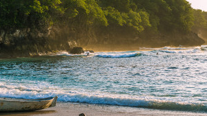 Local Kids surf on Waves in Sunset light, Beautiful Crystal Bay, Nusa Penida Bali