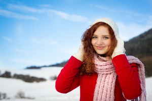Lonely girl wearing the red coat is posing in snowy country