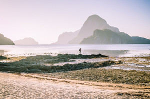 Lonely photographer on top of the rocks during low tide making photo on morning sunrise light in front of amazing Cadlao Island, El-Nido, Palawan, Philippines