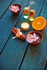 Lotus flower, cinnamon, orange, oils and burning candle on wooden table