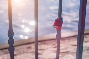Love lock or love padlock in front of a lake with sun reflection flares