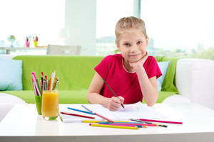 Lovely girl looking at camera while drawing with colorful pencils