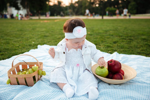 Lovely little girl sitting and choosing apple on picnic in park