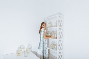 Lovely young woman in fishing net standing and putting gold fishes in jars on the shelf in the room