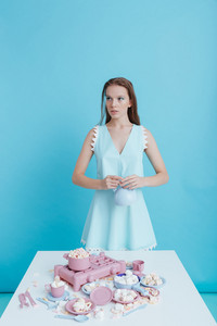 Lovely young woman standing in front of the table with plastic tableware and marshmallows over blue background