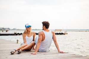 Loving couple sitting at the wooden pier and looking at each other