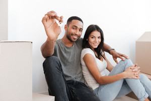 Loving couple sitting with unpacked boxes. Man holding key and showing it to camera. Looking at camera. Focus on key.
