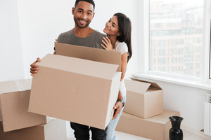 Loving couple standing near unpacked boxes. Woman hugging man and look at him. Man holding box in hands while looking at camera.