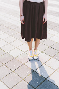 Low section of young woman standing on the road wearing long skirt and yellow baseball boots