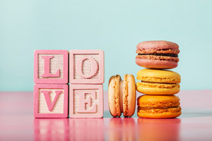Macarons with LOVE message on wooden blocks on pastel pink and blue background