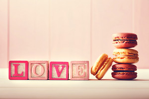 Macarons with LOVE message on wooden blocks on pink wooden wall