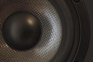 Macro / close-up of a bass and mid-tone loudspeaker / studio monitor element in kevlar.
