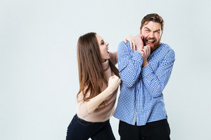 Mad aggressive young woman shouting and fighting with her husband over white background