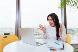 Mad angry young businesswoman screaming and using laptop in office