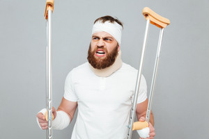 Mad bearded young man standing and holding crutches over white background
