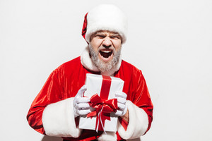 Mad irritated man santa claus holding present box and shouting