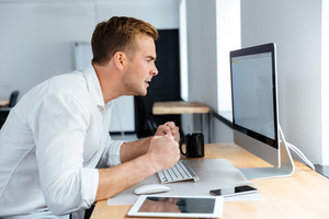 Mad irritated young businessman sitting and working with blank screen computer in office
