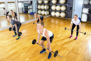 Male And Female Friends Exercising With Barbells In Gym