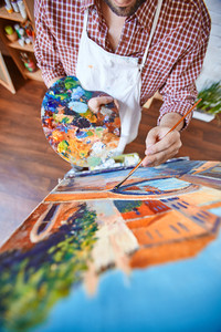Male artist painting with oil paints on canvas