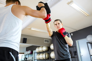 Male Boxer Punching Bag Held By Instructor In Gym