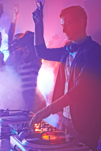 Male deejay mixing sounds on turntables with group of people dancing on background