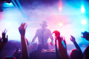 Male deejay standing by turntables in front of dancing crowd at disco