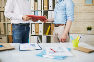 Male employee giving clipboard with papers to his colleague in office