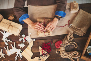 Male hands wrapping xmas gifts with various symbols of holiday near by