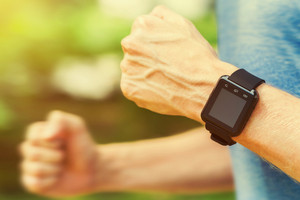 Male jogger running with a smartwatch outside in nature
