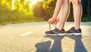 Male jogger tying his running shoes outside