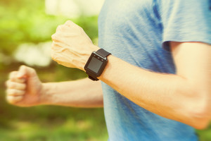 Male runner jogging outside with his smart watch in the sunlight