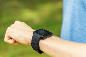 Male runner looking at his smart watch outside