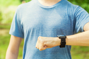 Male runner looking at his smartwatch outside