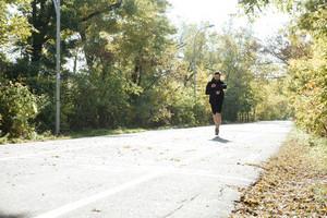 Male runner running in park. Full length portrait