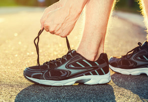 Male runner tying his shoes in preparation for a jog