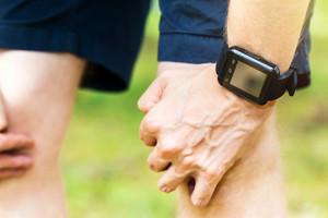 Male runner wearing a smart watch resting outside