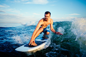 Male surfboarder practicing surfboarding