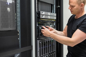Male Technician Installing Hard Drive In Datacenter