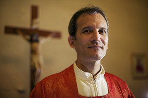 Man and faith, portrait of catholic priest on altar in church looking at camera and smiling